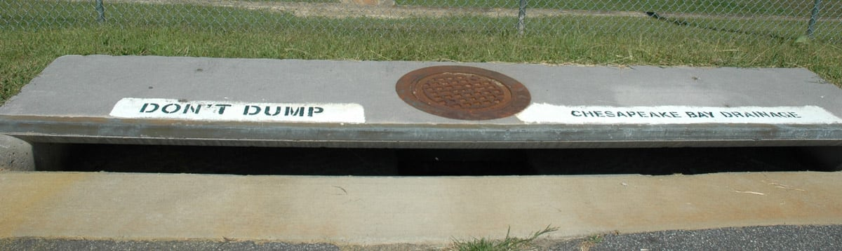 Storm drain labeled to inform public that it drains to waterways